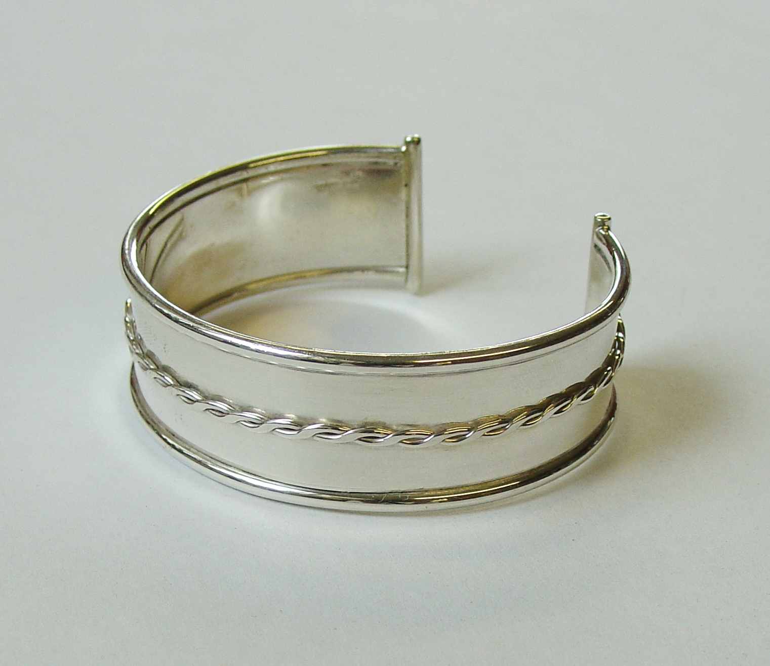 Chunky silver bangle with silver wire twist detail