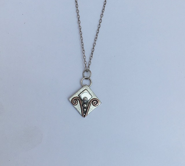 Silver pendant with copper detail